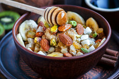 Organic oatmeal porridge with bananas, honey, almonds, pistachio, coconut, kiwi fruit, cinnamon, raisins in dark ceramic bowl Stock Images