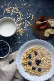 Organic oatmeal porridge with blueberry,banana, honey and milk, healthy lifestyle. Organic oatmeal porridge with blueberry, banana, honey and milk on dark stone Stock Image