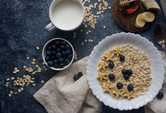 Organic oatmeal porridge with blueberry, banana, honey and milk, healthy lifestyle. Organic oatmeal porridge with blueberry, banana, honey and milk on dark stone Stock Photo