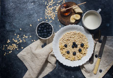 Organic oatmeal porridge with blueberry, banana, honey and milk, healthy lifestyle and diet concept Stock Photography