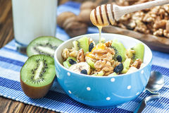 Organic oatmeal porridge. Organic oatmeal porridge in ceramic bowl with bananas, honey, walnuts, kiwi fruit and raisins. Healthy breakfast - health and diet Royalty Free Stock Image