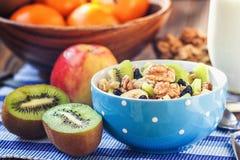 Organic oatmeal porridge in ceramic bowl with bananas, honey, walnuts, kiwi fruit and raisins. Healthy breakfast. Royalty Free Stock Photos