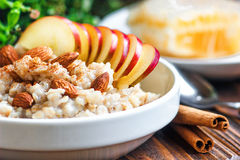 Organic oatmeal porridge in white ceramic bowl with apple, almond, honey and cinnamon. Healthy breakfast Royalty Free Stock Photos