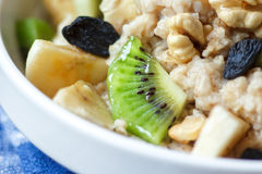 Organic oatmeal porridge. Organic oatmeal porridge in white ceramic bowl with bananas, honey, walnuts, kiwi fruit and raisins. Healthy breakfast - health and Royalty Free Stock Image