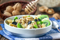 Organic oatmeal porridge. Organic oatmeal porridge in white ceramic bowl with bananas, honey, walnuts, kiwi fruit and raisins. Healthy breakfast - health and Royalty Free Stock Photography