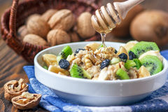 Organic oatmeal porridge. Organic oatmeal porridge in white ceramic bowl with bananas, honey, walnuts, kiwi fruit and raisins. Healthy breakfast - health and Royalty Free Stock Photos