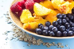 Organic oatmeal porridge in white ceramic bowl with raspberries, peaches and blueberries. Healthy breakfast - health and diet conc. Ept on the wooden table Royalty Free Stock Photo