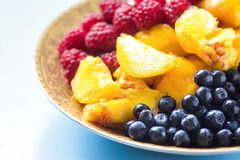 Organic oatmeal porridge in white ceramic bowl with raspberries, peaches and blueberries. Healthy breakfast - health and diet conc. Ept on the wooden table Royalty Free Stock Photography