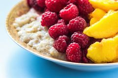 Organic oatmeal porridge in white ceramic bowl with raspberries, peaches and blueberries. Healthy breakfast - health and diet conc. Ept on the wooden table Royalty Free Stock Photos