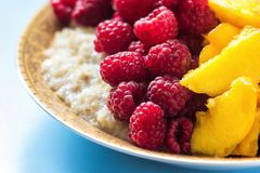 Organic oatmeal porridge in white ceramic bowl with raspberries, peaches and blueberries. Healthy breakfast - health and diet conc. Ept on the wooden table Royalty Free Stock Image
