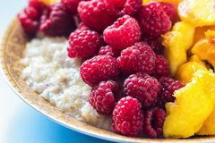 Organic oatmeal porridge in white ceramic bowl with raspberries, peaches and blueberries. Healthy breakfast - health and diet conc. Ept on the wooden table Stock Image
