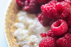 Organic oatmeal porridge in white ceramic bowl with raspberries, peaches and blueberries. Healthy breakfast - health and diet conc. Ept on the wooden table Stock Photography
