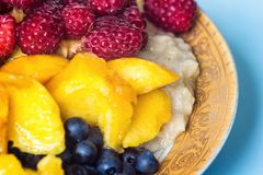 Organic oatmeal porridge in white ceramic bowl with raspberries, peaches and blueberries. Healthy breakfast - health and diet conc. Ept on the wooden table Royalty Free Stock Images