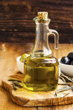 Organic olive oil bottle on rustic background Royalty Free Stock Image