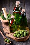 Organic olive oil with spices and herbs on an old wooden background. Healthy food. stock images