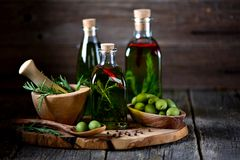 Organic olive oil with spices and herbs on an old wooden background. Healthy food. stock photos