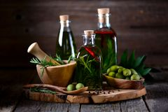 Organic olive oil with spices and herbs on an old wooden background. Healthy food.