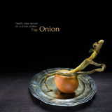Organic onion, served on a silver platter against a dark wood Royalty Free Stock Photography