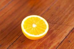 Organic orange fruit. Slices on wooden background Stock Photos