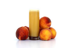 Organic Peach Juice. A glass of peach juice in front of peaches isolated on white background Royalty Free Stock Photo