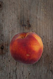 Organic peach on an old wooden board Royalty Free Stock Image