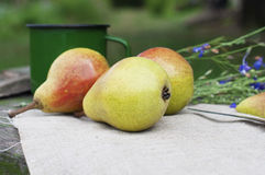 Organic pears on canvas with flowers and cup Stock Image