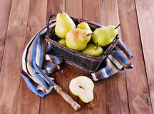Organic pears in a woven basket on wooden background Royalty Free Stock Photo