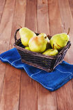 Organic pears in a woven basket on wooden background. Group of yellow pears in a rustic woven basket with blue napkin on a wooden background stock photos
