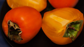 Organic Persimmons are delicious and exotic fruits in black plate, dark background Stock Photos