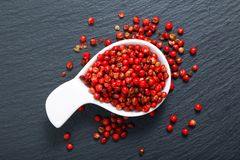 Organic Pink Peppercorn in white ceramic cup. On black slate stone background Royalty Free Stock Photos