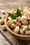 Organic pistachio nuts in bowl on wooden table. Closeup stock images