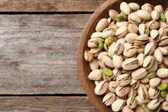 Organic pistachio nuts in bowl on wooden table, top view. Space for text stock photos