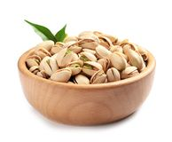 Organic pistachio nuts and leaves in wooden bowl. Isolated on white stock photo