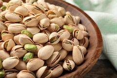 Organic pistachio nuts in plate on table. Closeup stock photography