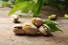 Organic pistachio nuts in shell. On wooden table royalty free stock images
