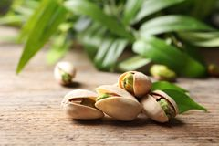 Organic pistachio nuts in shell on table. Organic pistachio nuts in shell on wooden table stock images