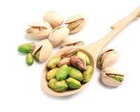 Organic pistachio nuts and spoon on white background. Closeup stock photos