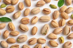 Organic pistachio nuts on white background. Flat lay royalty free stock image