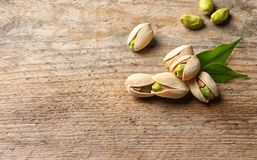 Organic pistachio nuts on wooden table. Space for text royalty free stock photography