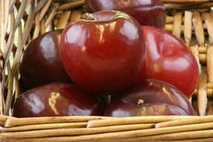 Organic plums in a wicker basket. Some organic plums in a wicker basket Stock Photo