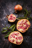 Organic pomegranate cut in half on a rusty background Stock Photography