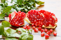 Organic pomegranate fruit on a wood table- Shallow DOF Royalty Free Stock Photos