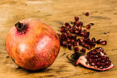 Organic pomegranate on a wooden table Royalty Free Stock Photography