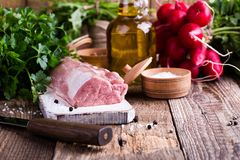 Organic pork meat. On chopping board and food ingredients ready for cooking, rustic style, selective focus Royalty Free Stock Photos