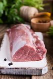 Organic pork meat. On chopping board and food ingredients ready for cooking, rustic style, selective focus Stock Photo