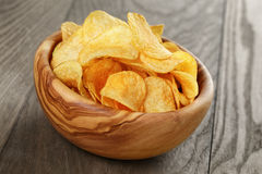 Organic potato chips in bowl on wood table Royalty Free Stock Photo