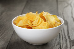 Organic potato chips in white bowl on wood table Stock Image