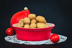 Organic potatoes in the red ceramic bake pot, tomatoes and pumpkin Stock Photo