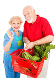Organic Produce is AOkay. Senior couple shopping for organic produce and giving the okay sign.  Isolated on white Royalty Free Stock Image