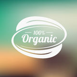 Organic product badge on blurred landscape. Vector illustration Royalty Free Stock Photo